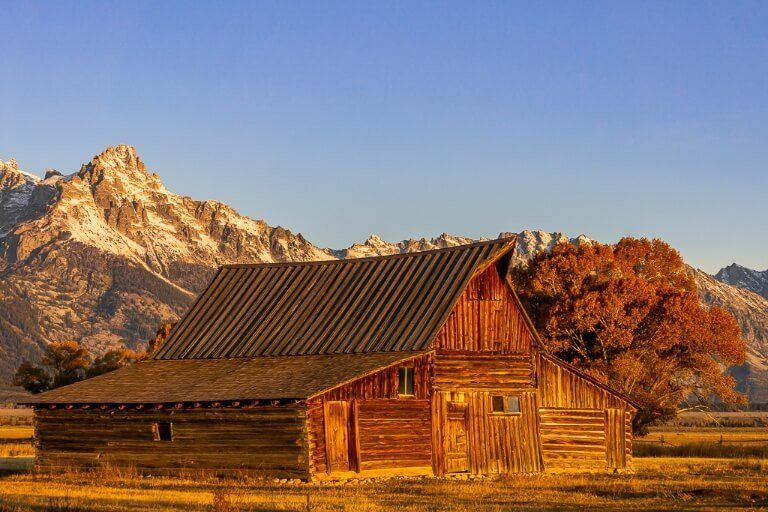 Mormon Row moulton barn at sunrise in Grand Teton National Park Wyoming best place to stop on a salt lake city to yellowstone road trip itinerary