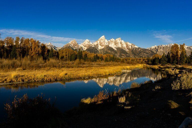 Schwabacher Landing Grand Teton national park at sunrise deep shadows foreground snake river and yellow meadows with mountains background reflecting