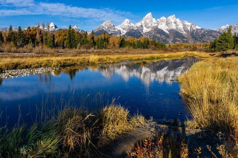 Snow capped mountains reflecting in almost still river with grass and trees surrounding
