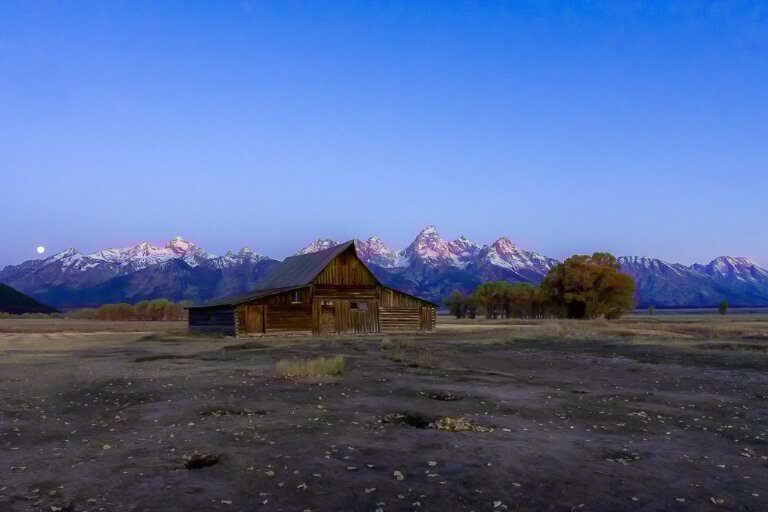 Mormon Row with teton range glowing red at first light