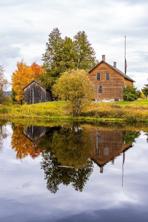 Stunning photography John Brown Farm Barn Historic building and barn with fall foliage colors trees oranges and yellows reflecting in a small pond in adirondacks new york