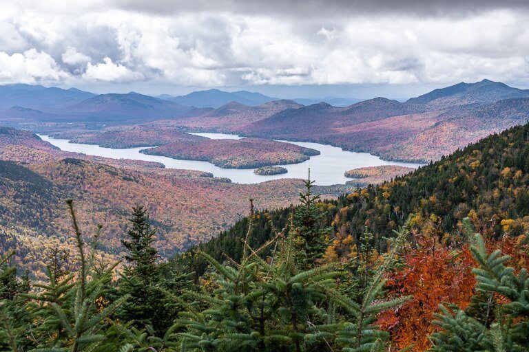 Best things to do in Lake Placid New York Adirondacks including this stunning view over Champlain Lake from Little Whiteface after taking cloud splitter gondola in fall with stunning foliage and clouds