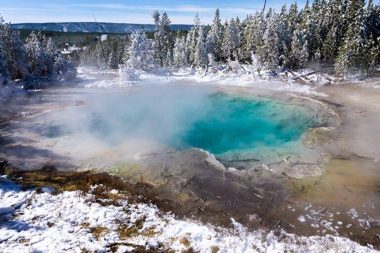 Turquoise hot spring surrounded by snow and trees