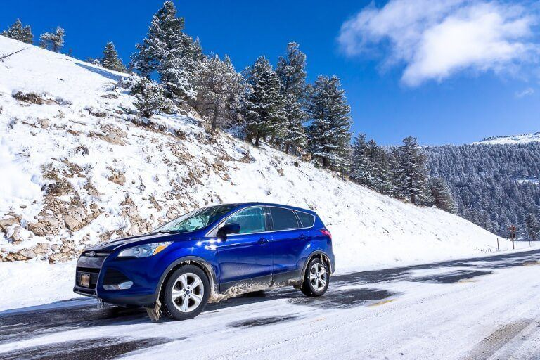 Car on road with snow on ground in wyoming