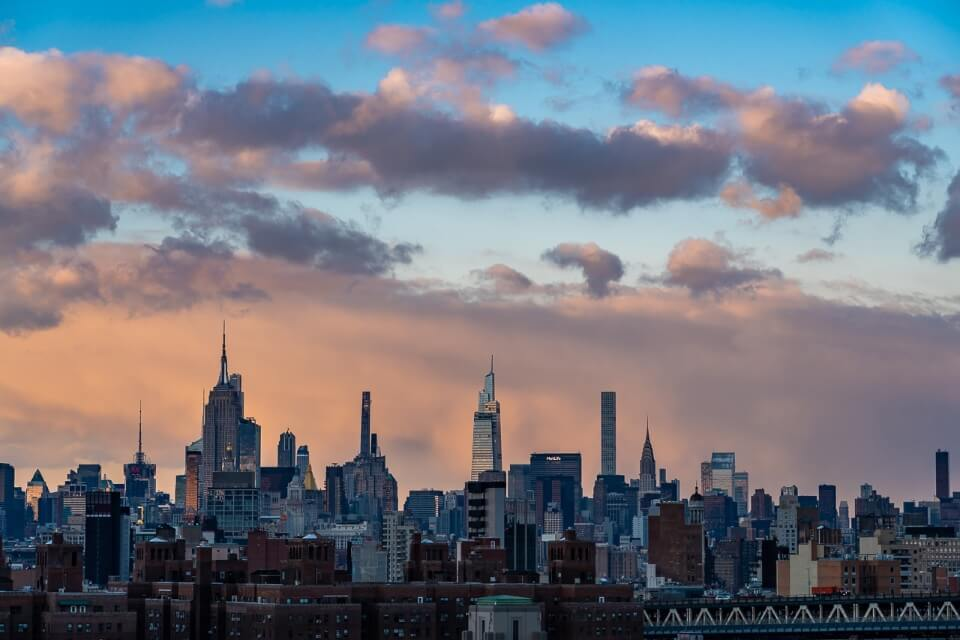 Midtown Manhattan from Brooklyn Bridge at Sunset with stunning colors and puffy clouds over New York City photography