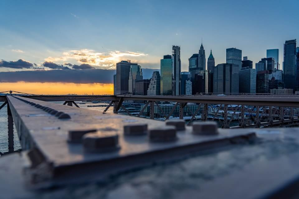Steel girder with bolts and manhattan skyline at sunset in NYC