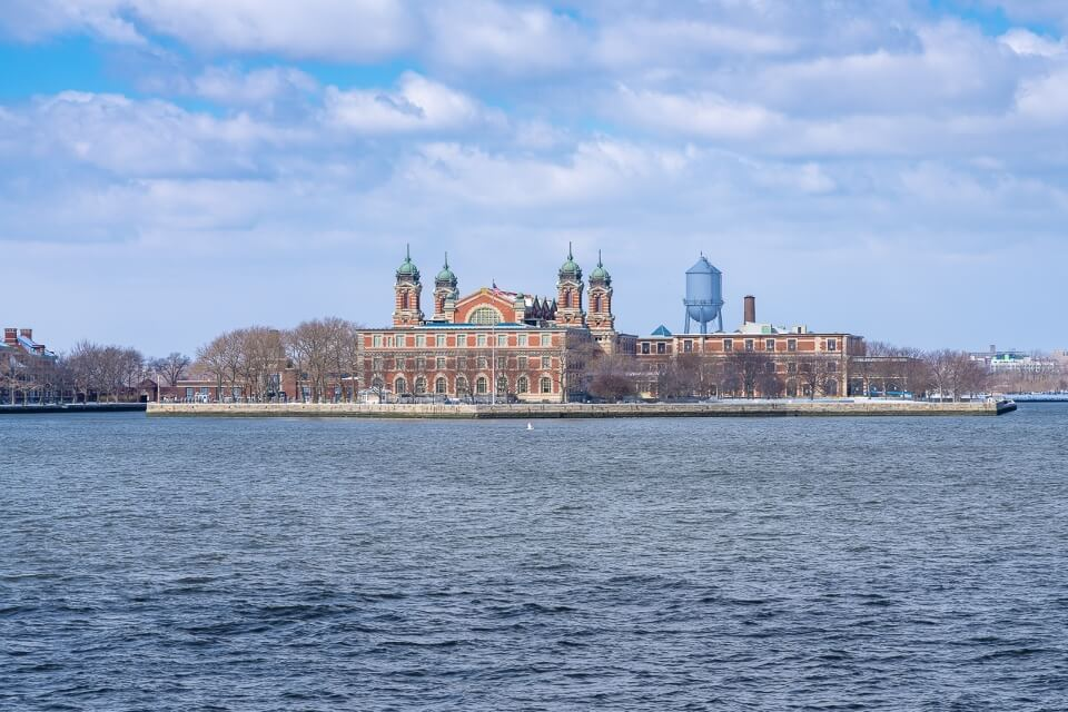 Ellis Island from afar on the river hudson huge building and water tower visible