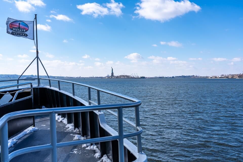 Boat on river heading towards island in new york city