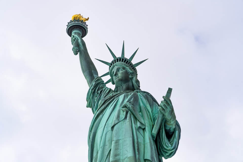 Statue of Liberty on liberty island is one of the best things to do in lower manhattan new york city itinerary green statue and yellows torch in grey clouds