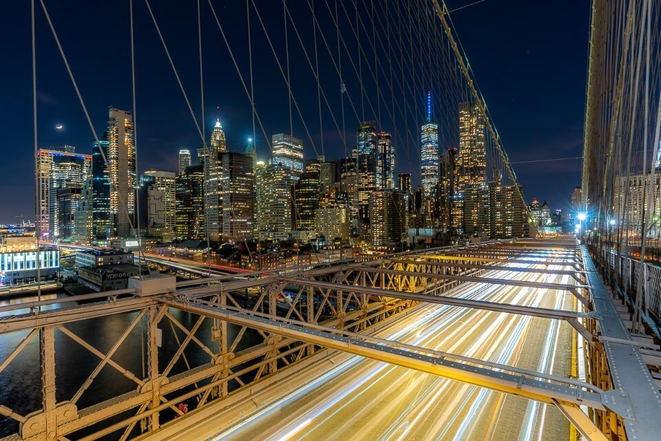 Cars driving across brooklyn bridge photography long exposure blur effect with car lights and manhattan skyline in background at night