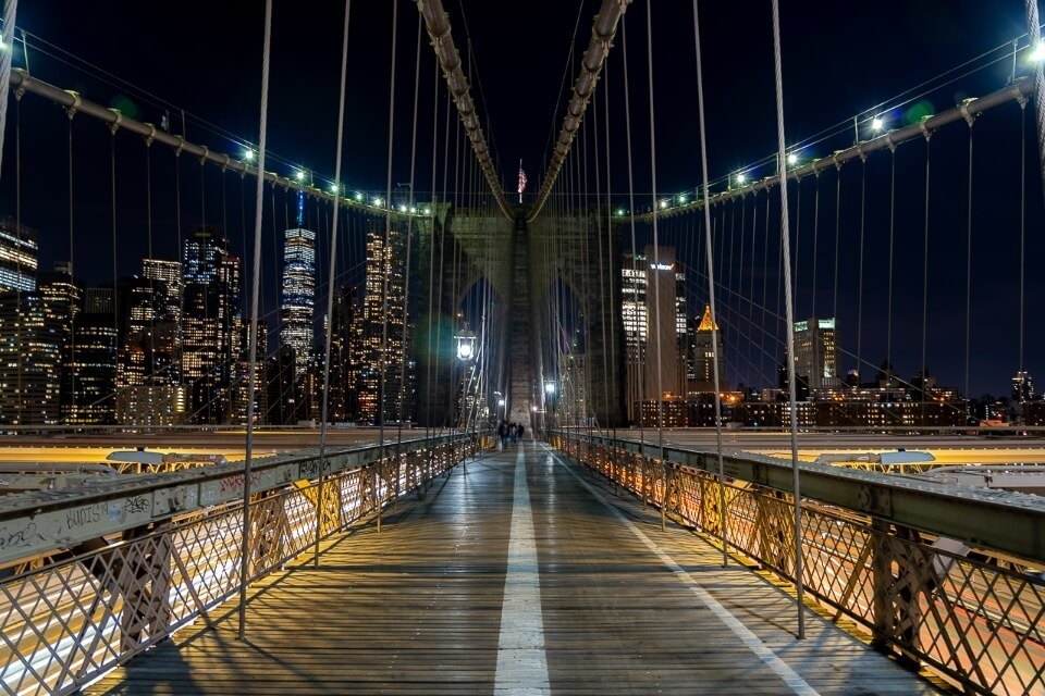 Walking along a path in darkness in new york city with manhattan behind