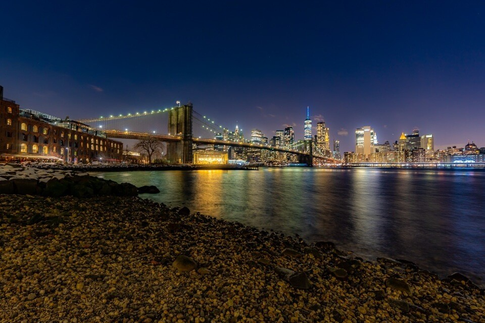 Brooklyn Bridge at night photography taken from Pebble Beach in Brooklyn colors reflecting in river in NYC