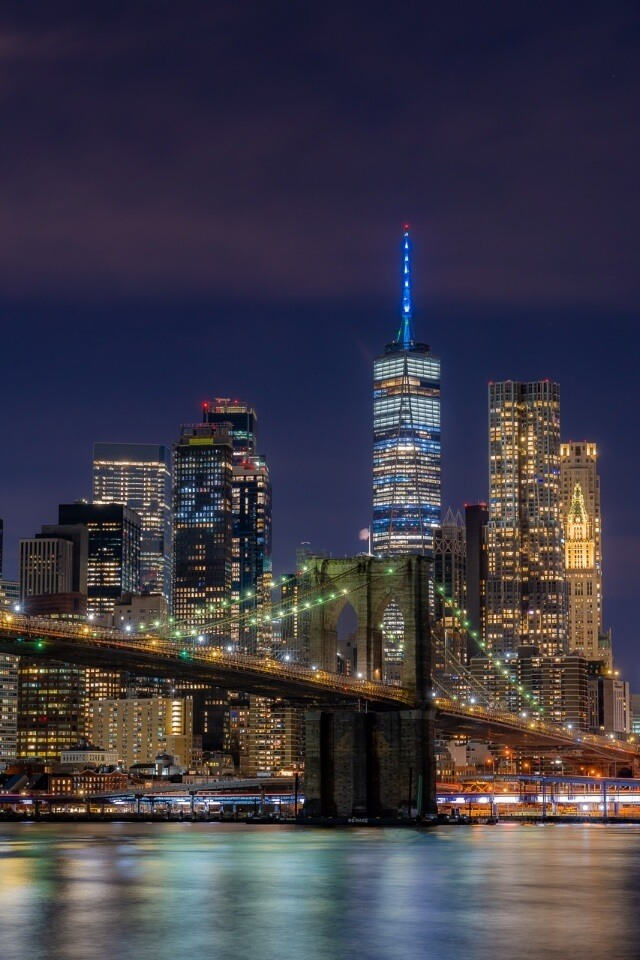 Manhattan skyline from Brooklyn with bridge foreground and one world trade center in background with blue spire new york city photography