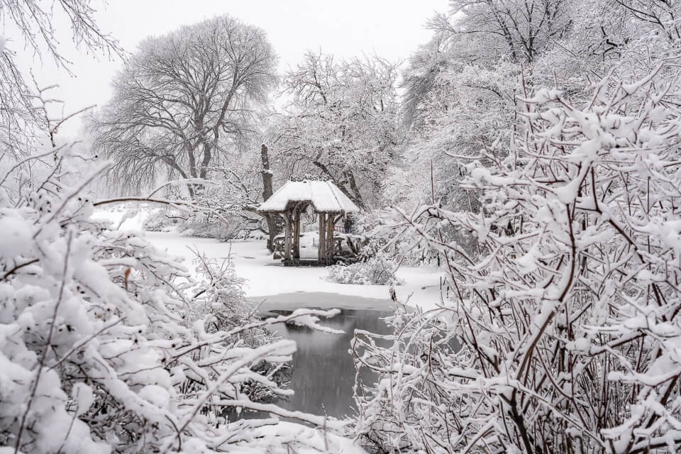 Wagner Cove wooden shelter on a winter snow day in central park from a viewpoint over frozen lake