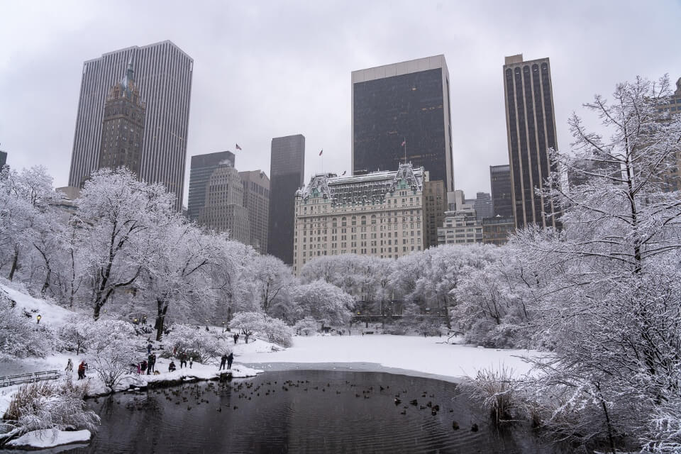 Plaza hotel and NYC skyline from Gapstow Bridge in southeast central park on a snow winter day