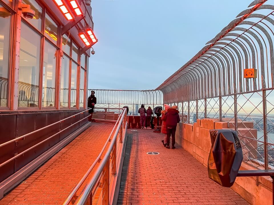 Empire State Building has a mesh fence with diamond shaped holes on its observation deck and a red glow