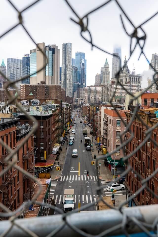 Madison street Chinatown through hole in fence photography manhattan bridge walk to brooklyn
