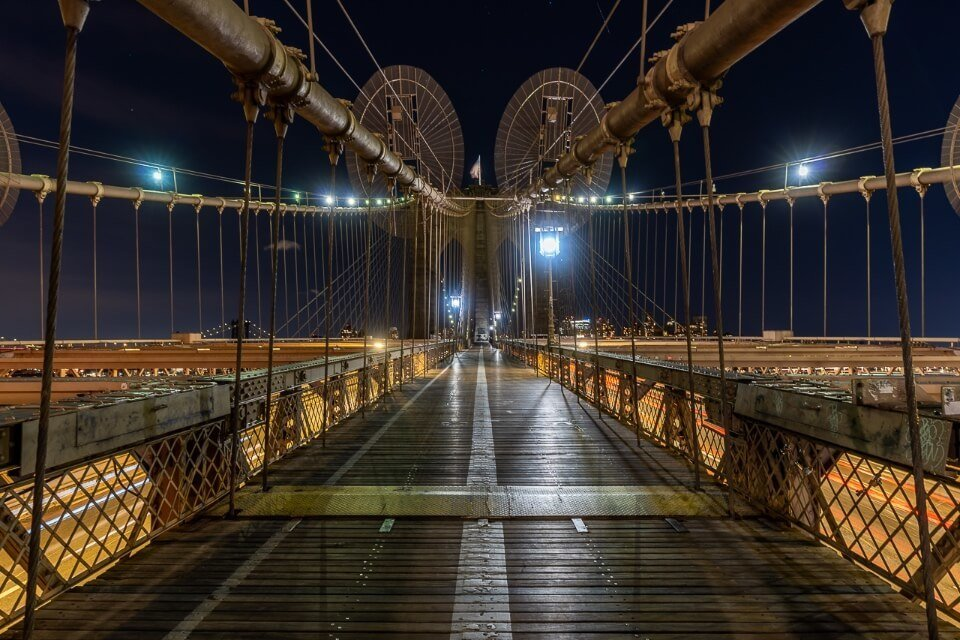 Brooklyn Bridge lit up at night with nobody on the wooden pedestrian path
