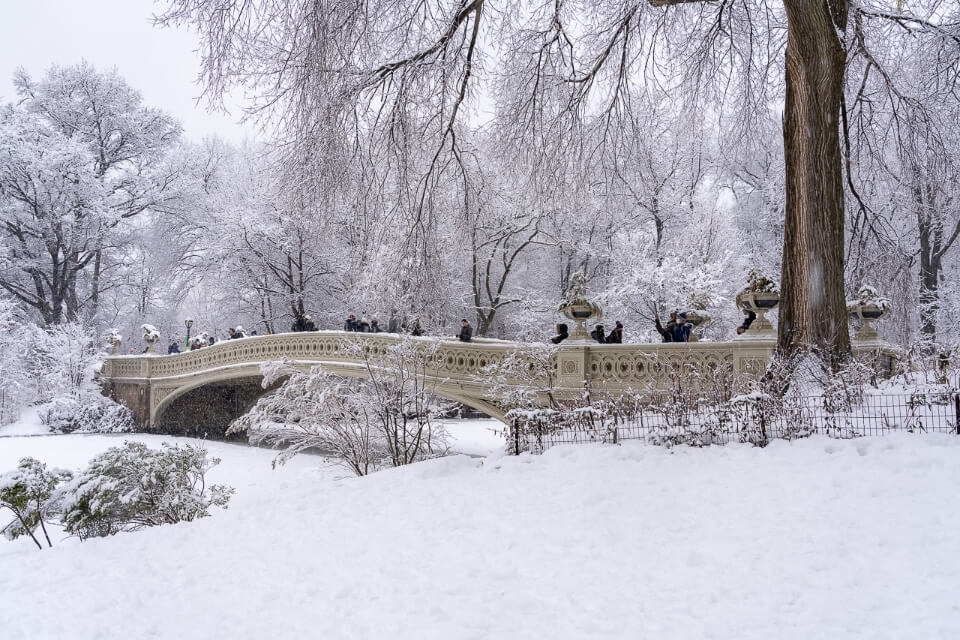 Central Park Bow Bridge in snow and ice winter plan a trip to nyc