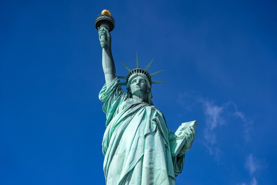 Statue of liberty is unmissable on a 4 days in new york city itinerary for first time visitors lady liberty holding torch high into the blue sky