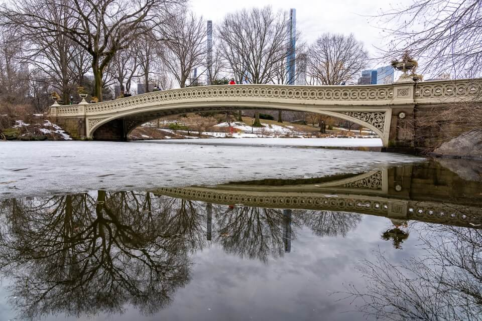 Bow bridge in central park reflecting in water on a snowy day in winter