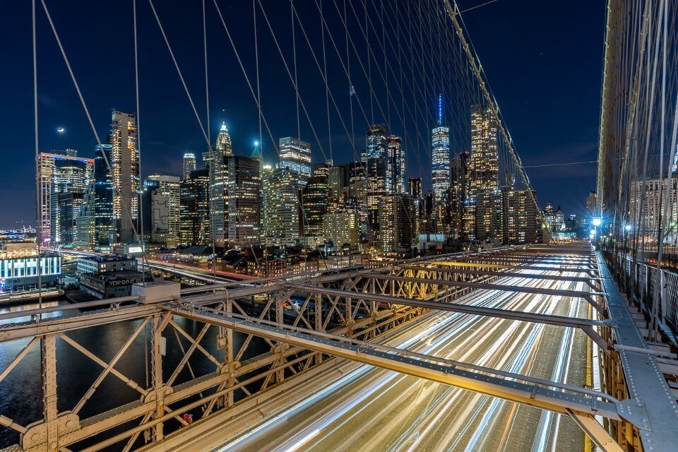 Lower Manhattan illuminating at night with long exposure creating light effect on Brooklyn Bridge one of the very best NYC photography locations of all