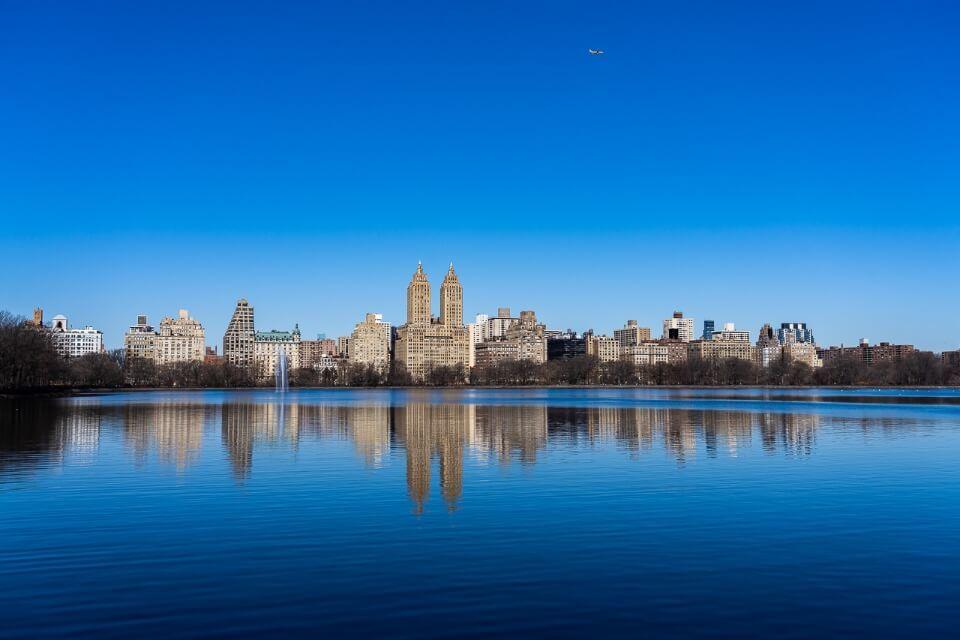 Jacqueline Kenny Onassis reservoir deep blue reflecting upper west side buildings and el dorado