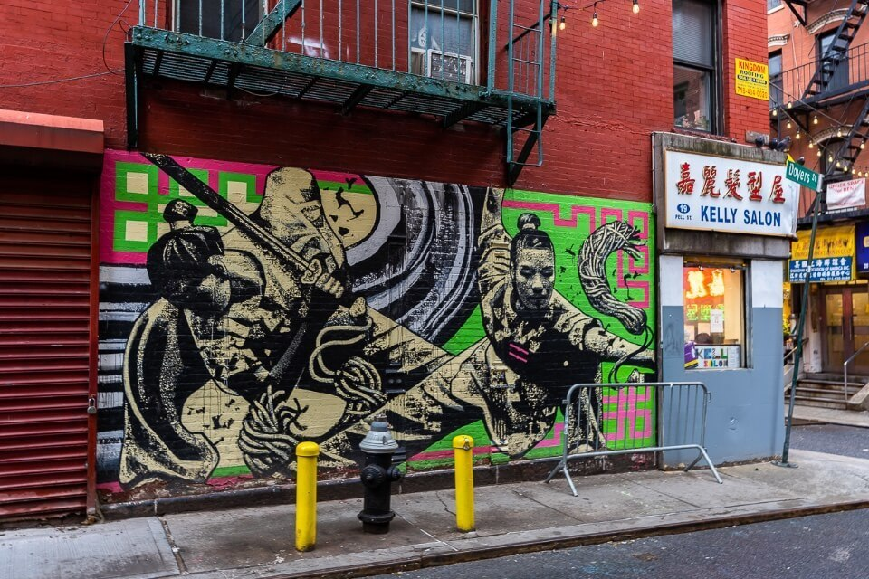 Chinatown in New York City mural on wall with chinese shops and orange brick walls