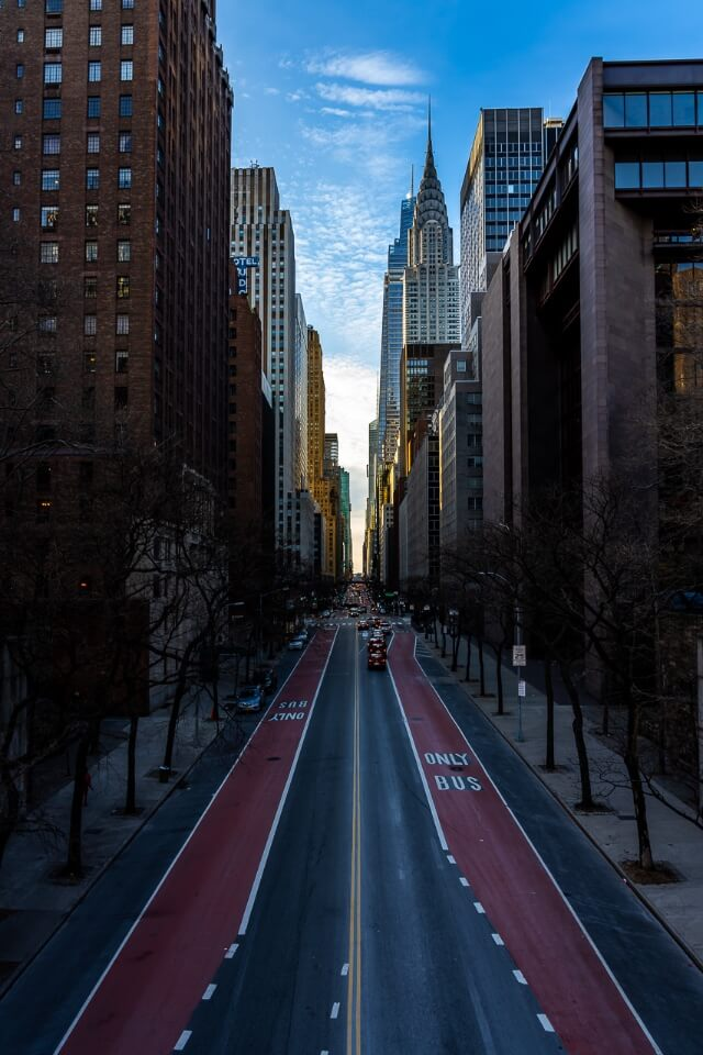 Manhattanhenge is one of the most unique and stunning NYC photography locations looking directly through buildings past chrysler building at sunset