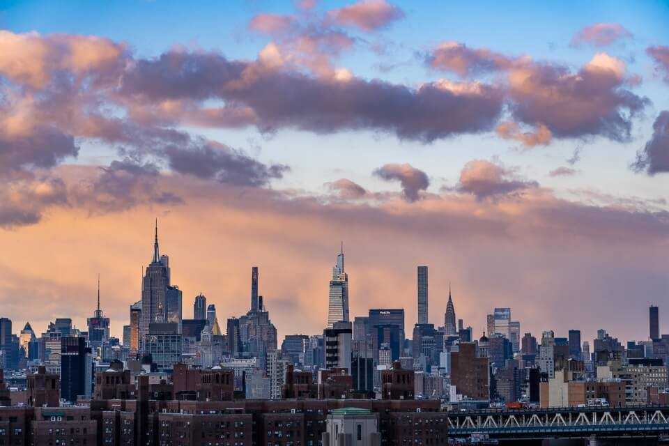Midtown Manhattan famous buildings from Brooklyn Bridge during sunset with an incredible sky