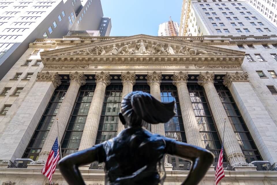 Fearless girl statue looking up at NYSE in financial district lower manhattan