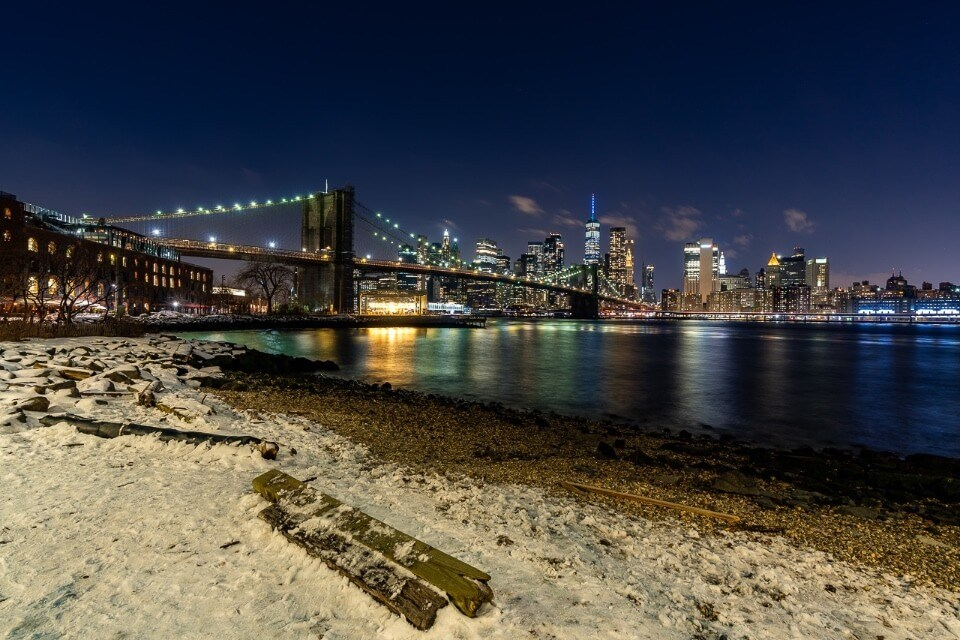 Pebble Beach view of janes carousel time out market and nyc skyline in background behind Brooklyn bridge with snow on beach