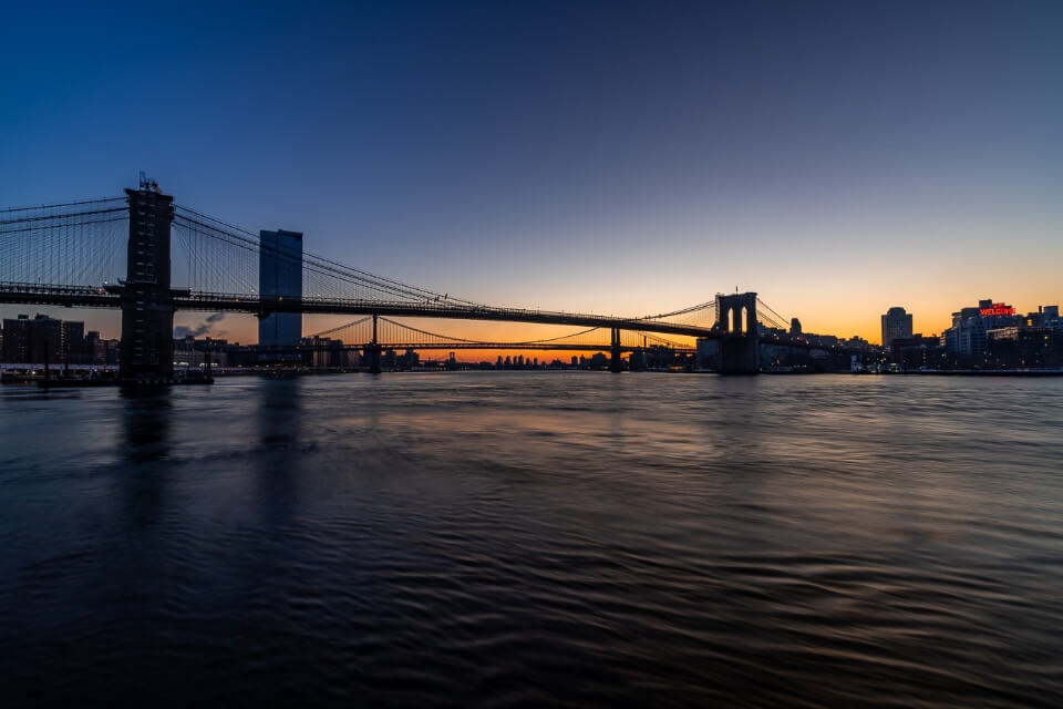 Brooklyn Bridge at sunrise taken from Pier 17 stunning colors in the sky one of the best hidden photography locations in NYC