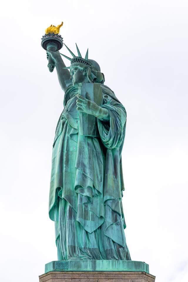 Statue of Liberty is an iconic NYC photography location not to be missed on any visit close up against grey sky accentuating green color