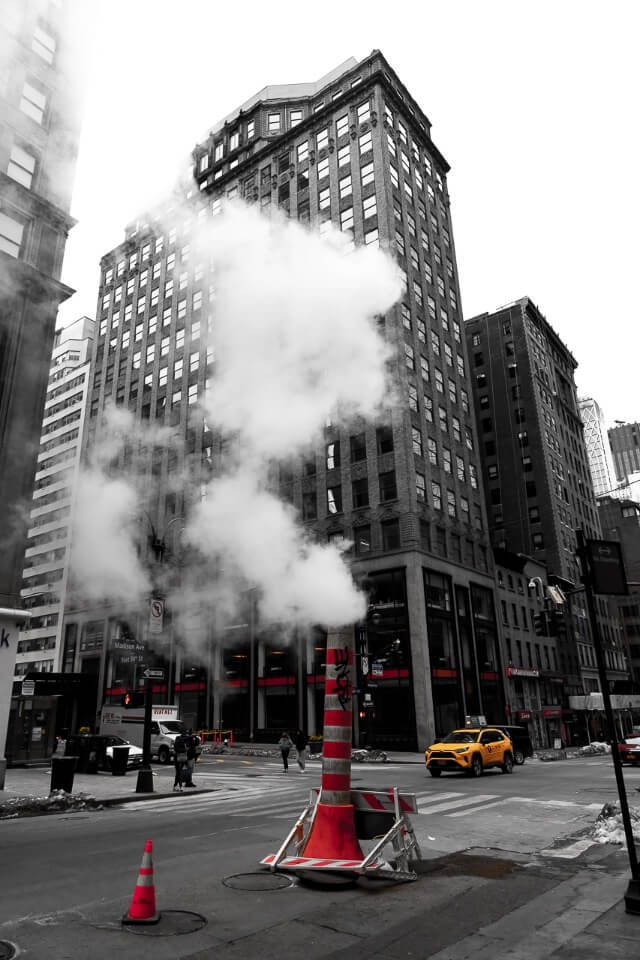 Smoke stake from subway surrounded by buildings