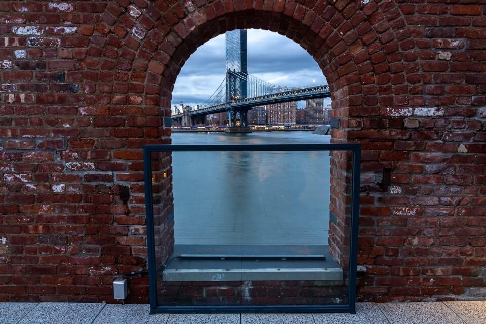 Hidden gem NYC photography location Manhattan Bridge through an arched brick window