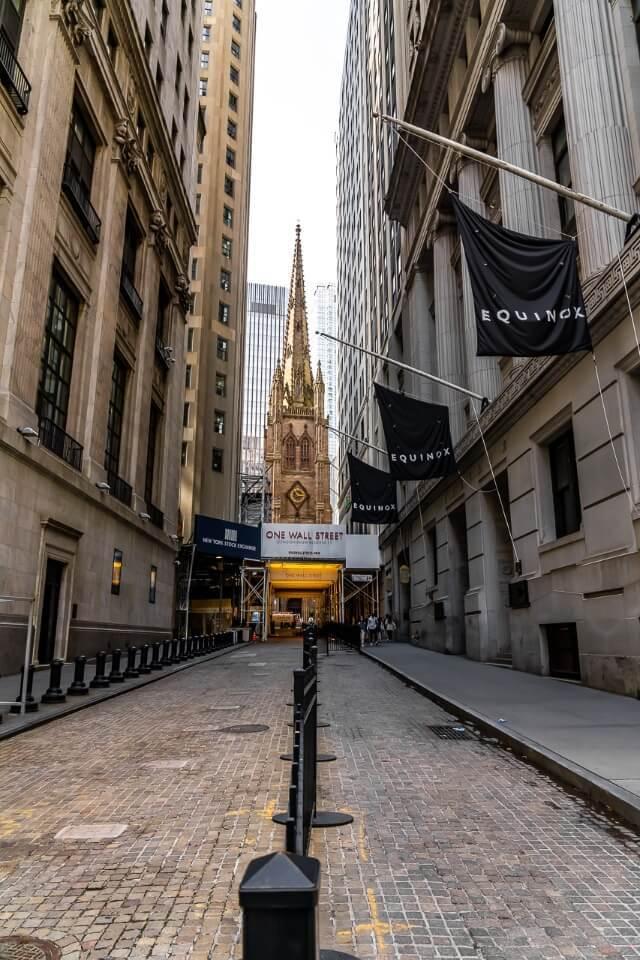 Wall Street leading through the narrow buildings to Trinity Church