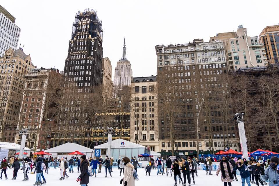 Ice skaters in bryant park with empire state building peaking over building tops