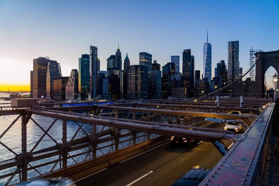 Lower Manhattan NYC skyline from Brooklyn Bridge at sunset