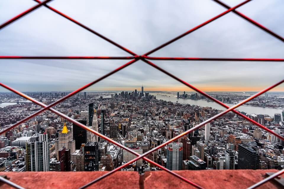 Empire state building is one of the best things to do in new york city on a first visit got to 82nd floor for this view over the city through mesh fence