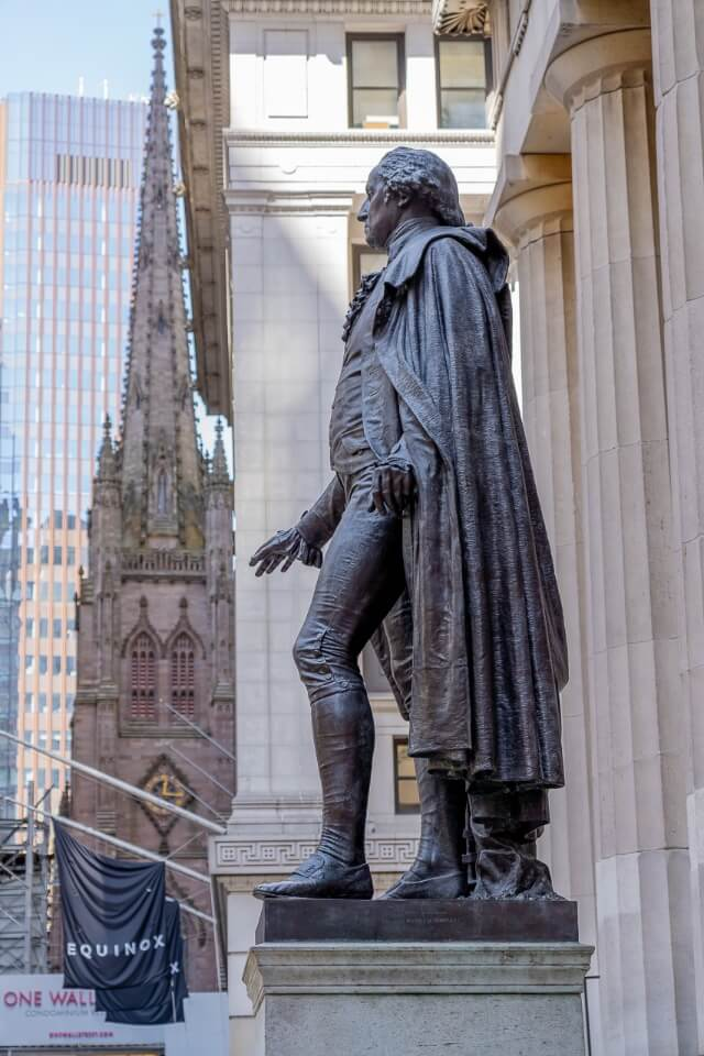 George Washington statue at federal hall on wall street and trinity church in background one of the best places to visit on a first trip to new york city