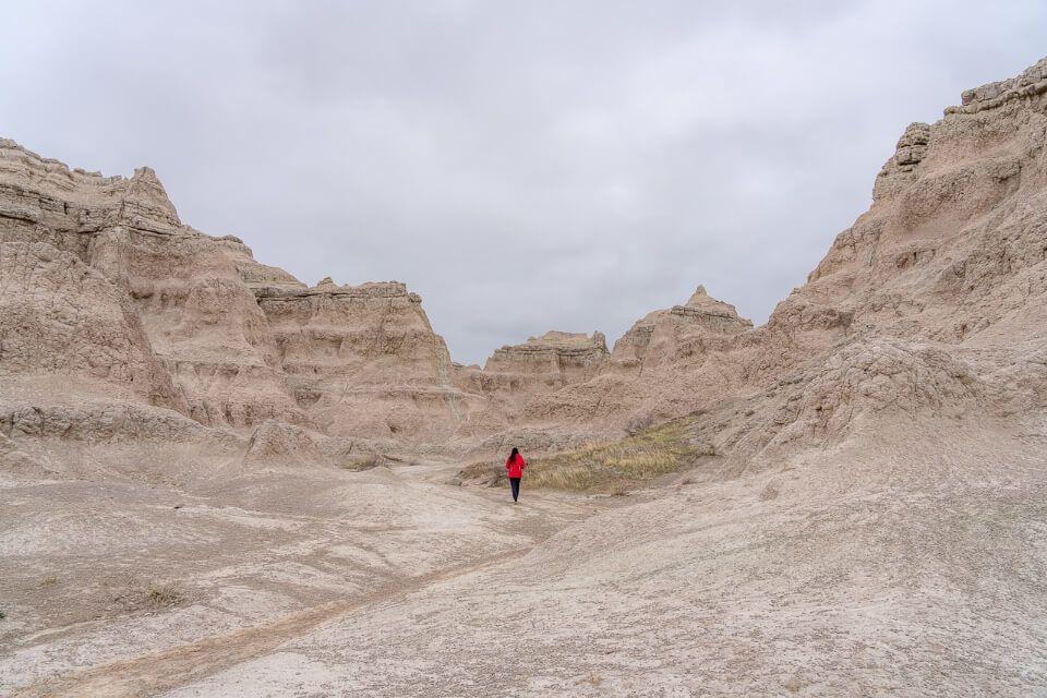 Woman walking through rocks on the badlands wall notch trail hike