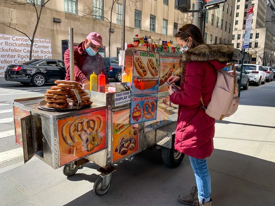 Buying a hotdog from a hotdog stand on fifth avenue in new york city