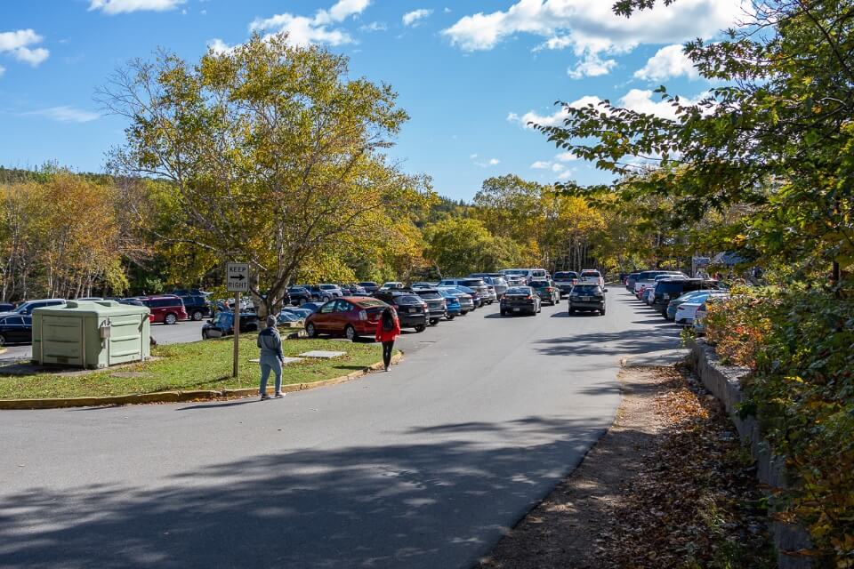 Parking lot filled with cars and people walking