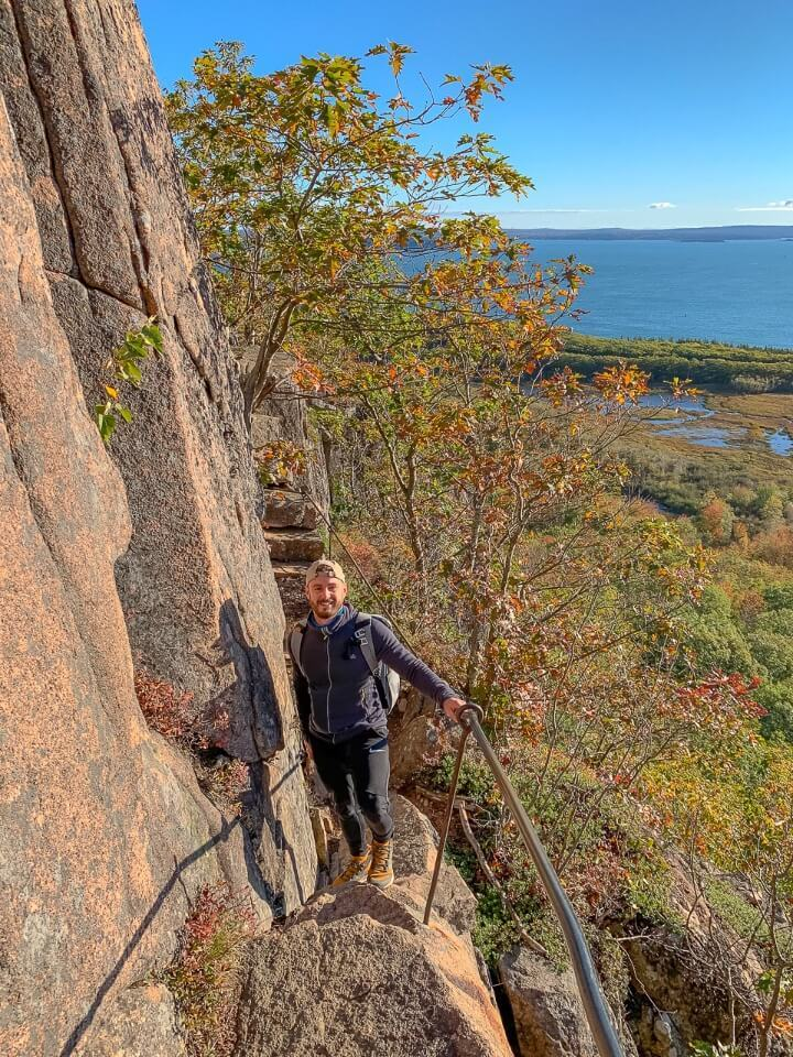 Man standing on very narrow rocky ledge with iron rail and stunning views over the ocean