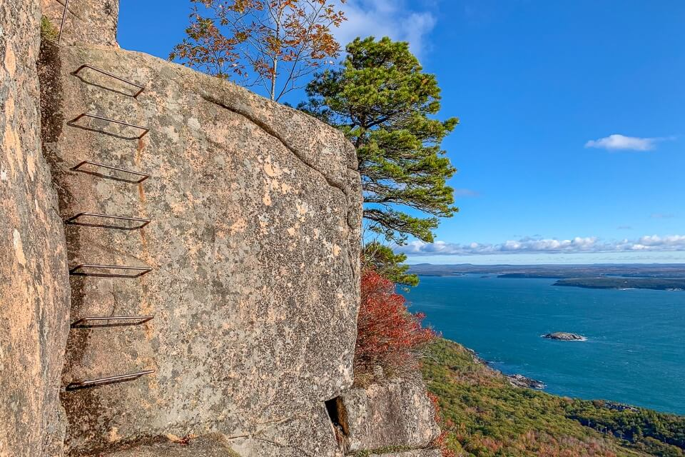 Beautiful image of an iron rung ladder in a granite rock face with views over the ocean and colorful trees precipice trail hike in acadia national park maine