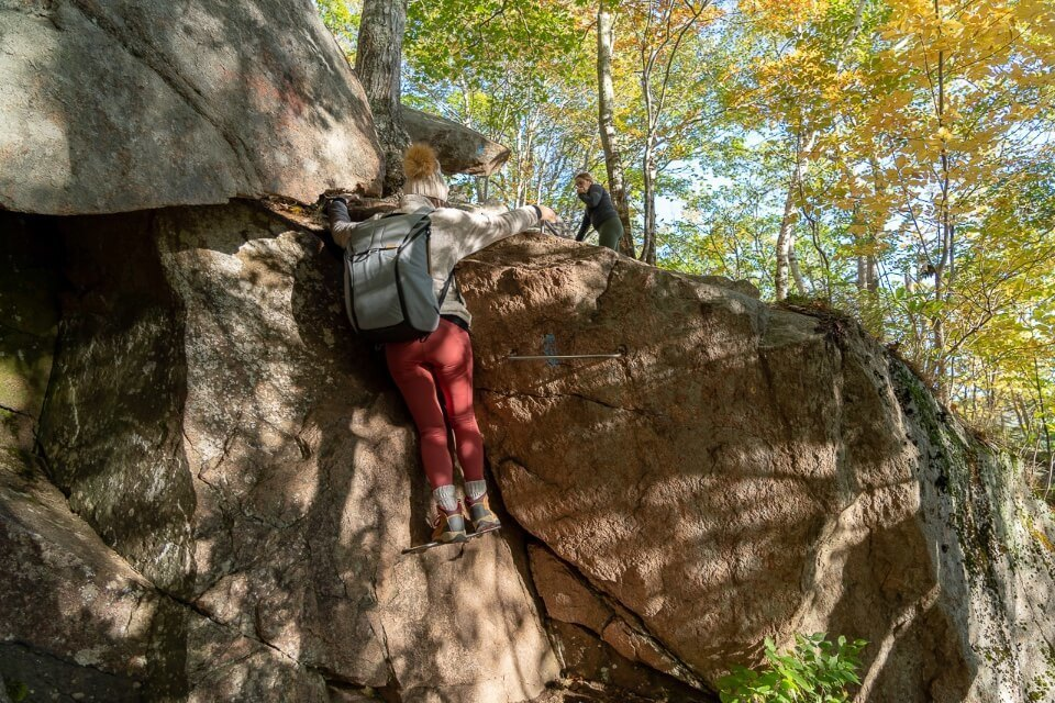 Woman climbing boulder with iron rung ladder in a forest