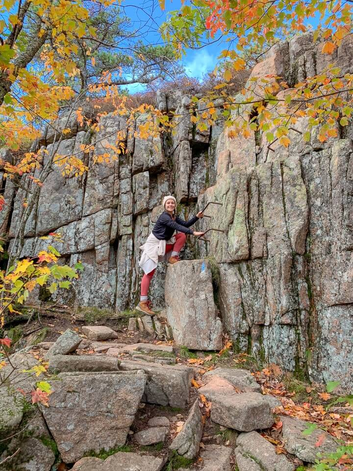 Woman climbing iron ladders on a stunning hike in maine