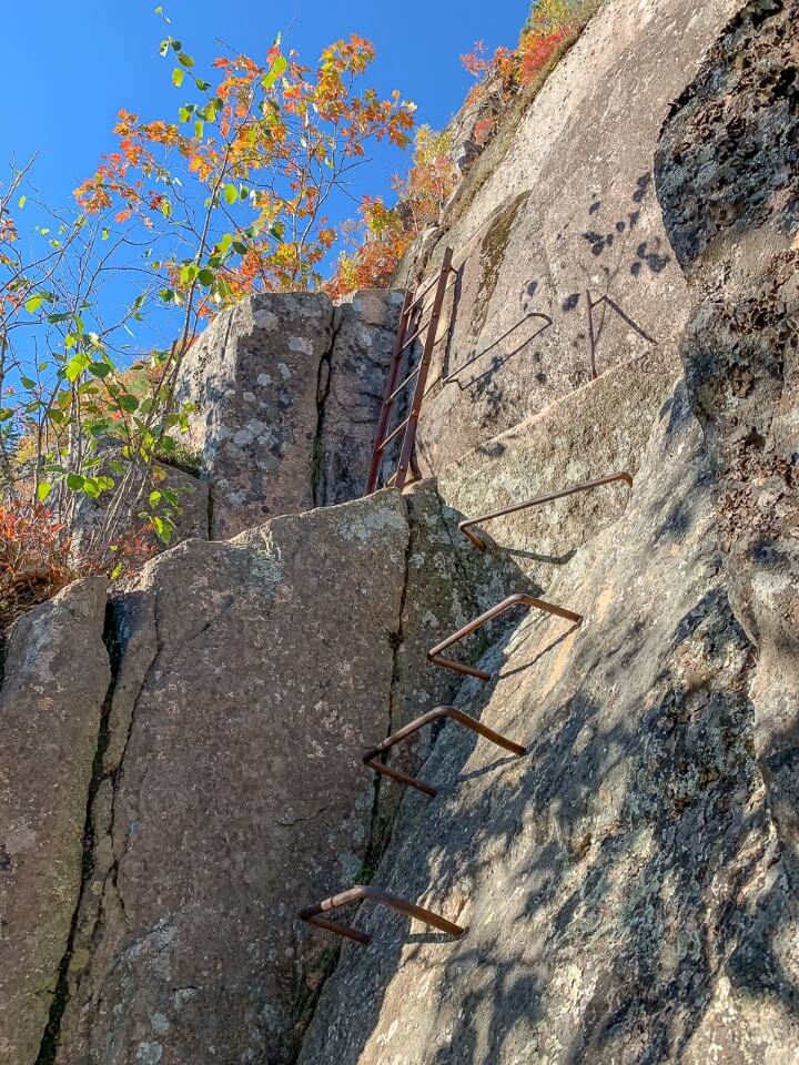 Ladders made of iron bars in rock on the side of precipice trail hike acadia