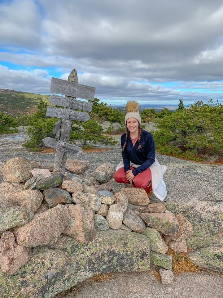 Woman at the champlain mountain summit sign after hiking the precipice trail in acadia